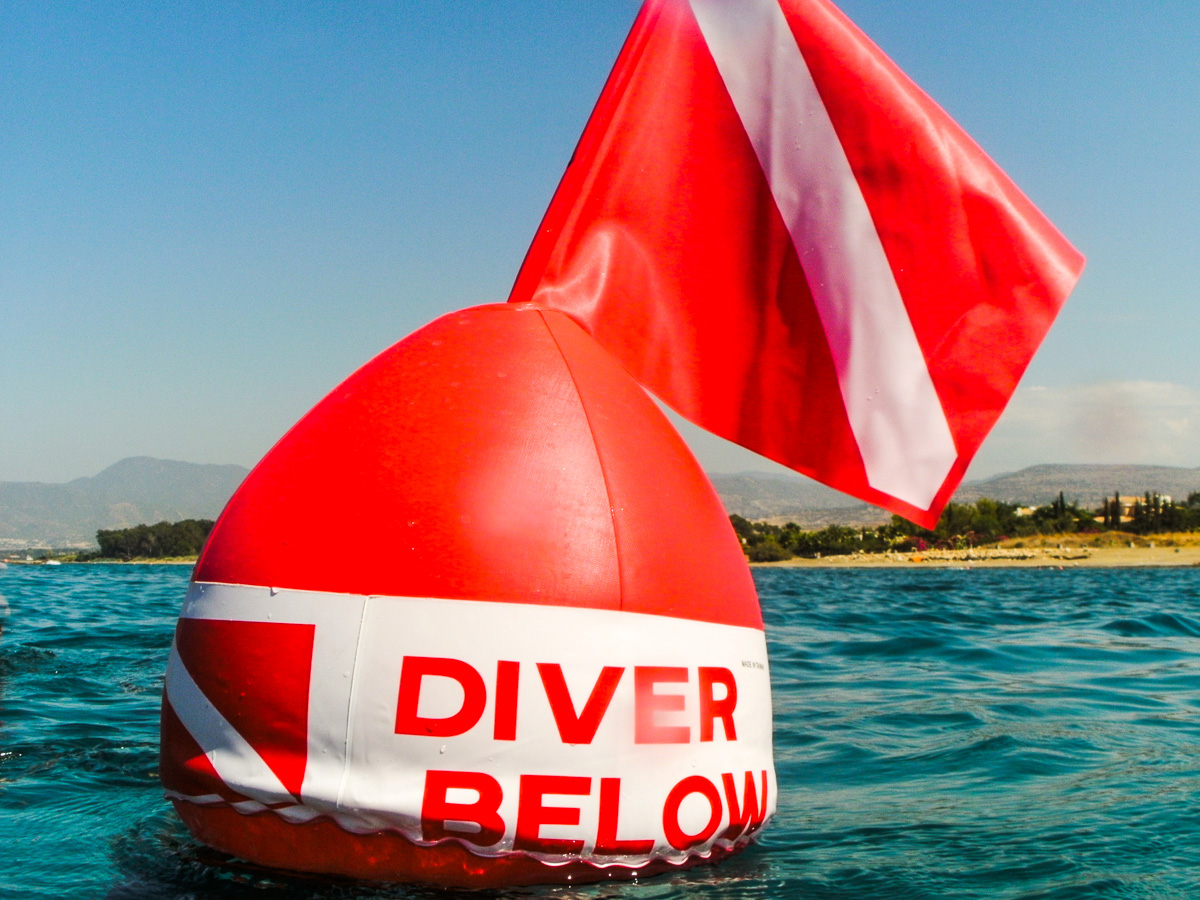 Cool Divers Latchi - Diver below red sign at sea level
